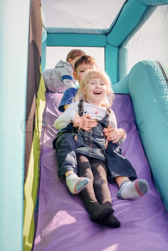Stock image of 'Adorable young brother and sister going down outdoor inflatable bouncy slide in purple and blue'