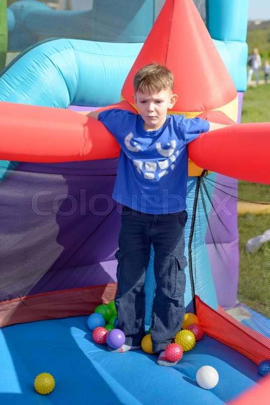 Stock image of 'Handsome little boy standing on a bouncy castle surrounded by balls in spring sunshine at a fairground or amusement park'