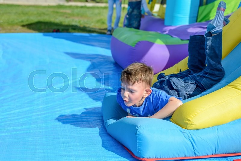Stock image of 'Handsome little boy lies on a bouncy castle surrounded by balls in spring sunshine at a fairground or amusement park'