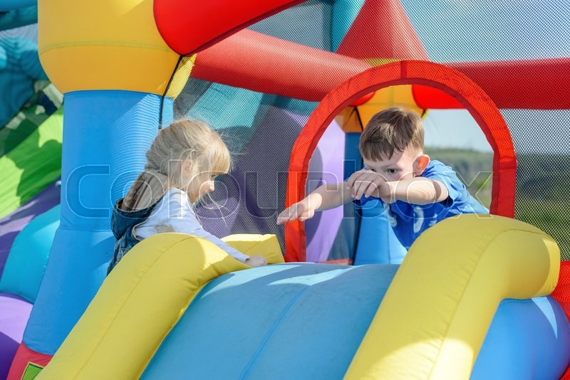 Stock image of 'Little children climbing and leaping on red, blue and yellow giant inflatable bouncy slide outdoors during sunny day'