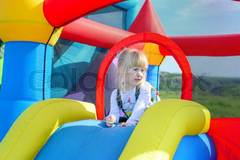 Stock image of 'Cute little happy girl laying down on top of blue, red and yellow inflatable outdoor bouncy carnival amusement slide'