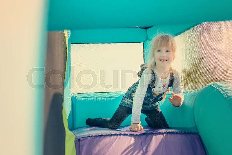 Stock image of 'Single little happy blond girl dressed in blue jeans skirt getting ready to go down inflatable purple and green outdoor slide'
