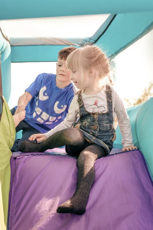 Stock image of 'Cute young brother and sister having fun as they get ready to go down inflatable purple and green outdoor slide'