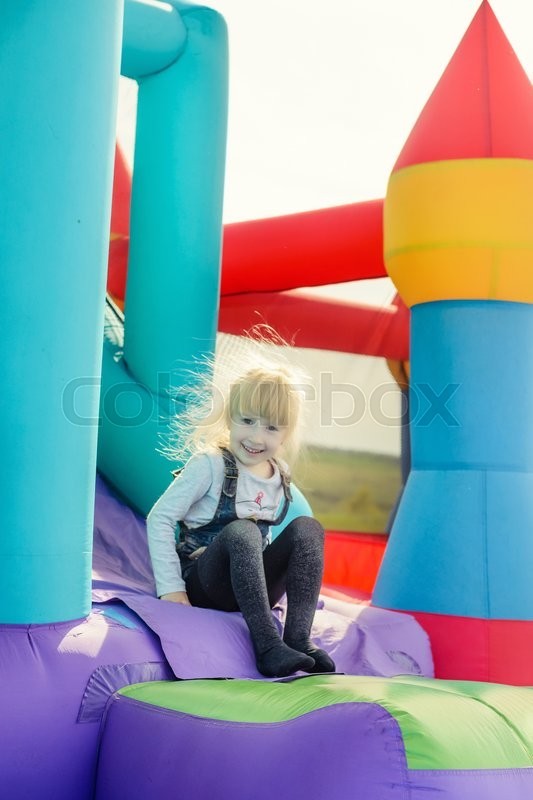 Stock image of 'Single happy cute little girl with blond hair in blue jean skirt at bottom of inflatable bouncy slide'