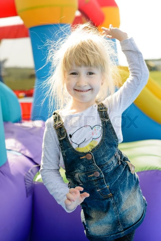 Stock image of 'Cheerful cute little girl with blond hair standing on end in blue jean skirt dancing next to inflatable castle and slide outdoors'