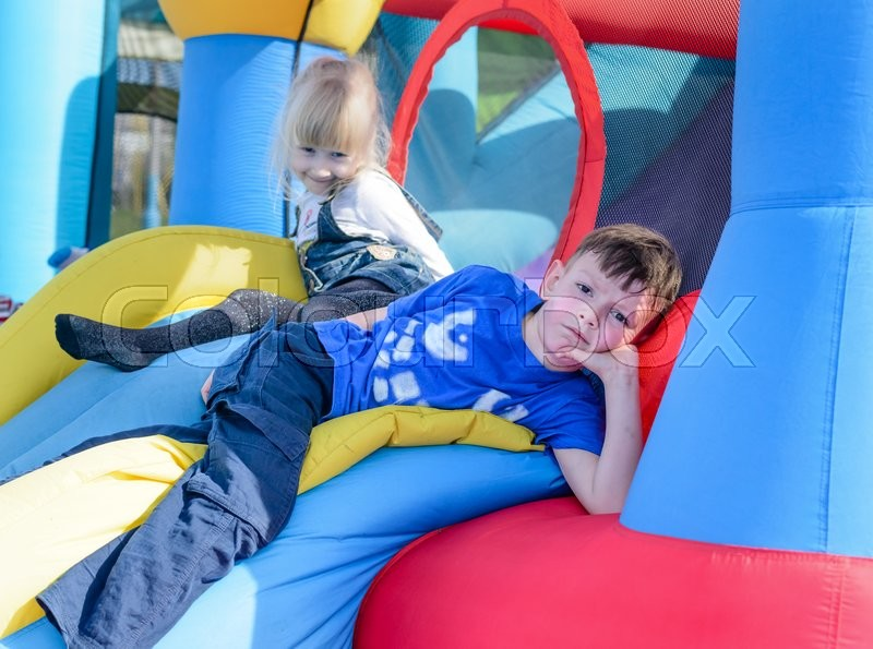 Stock image of 'Cute young brother and sister having fun as they lay down on inflatable blue, yellow and red castle and slide'
