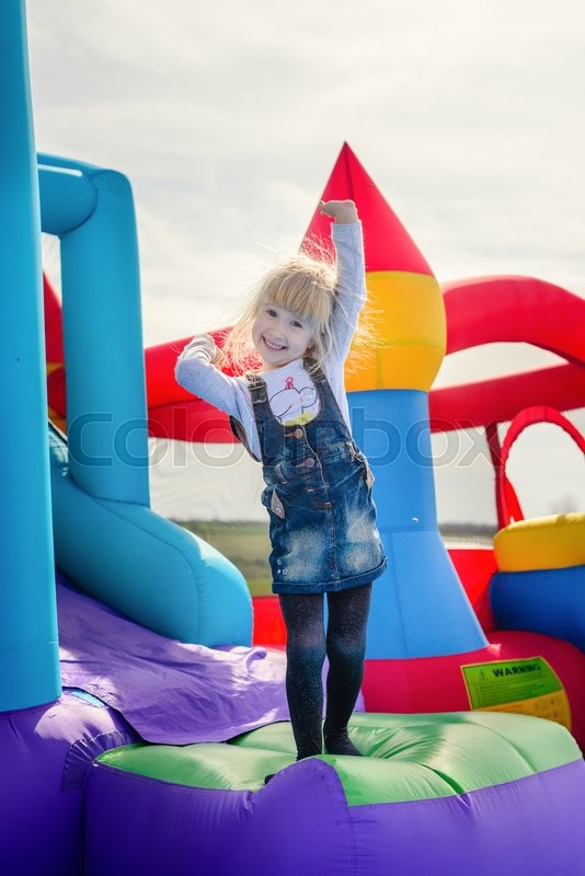 Stock image of 'Single excited cute little girl with blond hair in blue jeans jumping and waving from inflatable blue bouncy slide'