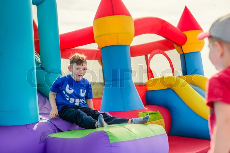 Stock image of 'Two little boys in short sleeve shirts playing on inflatable slide and castle outdoors'