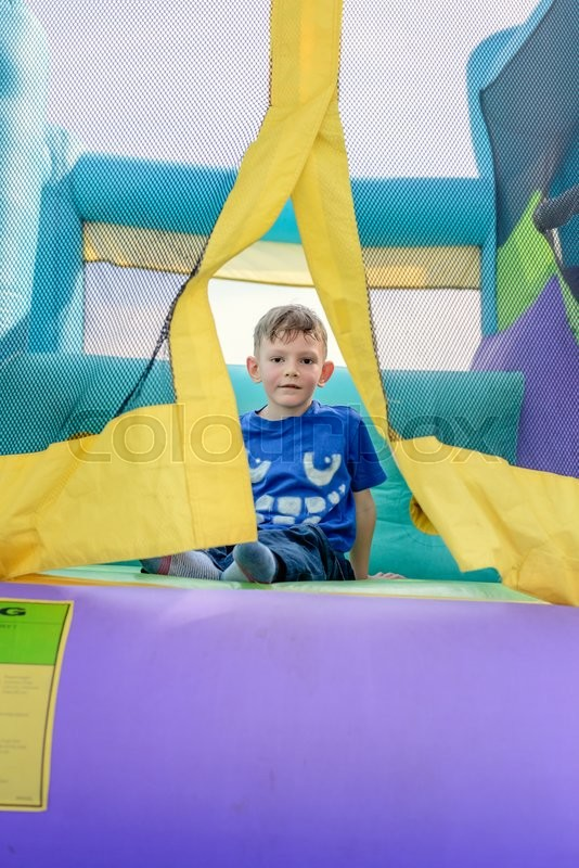 Stock image of 'Single cute little curious boy with sweaty face looking from entrance of bouncy house'