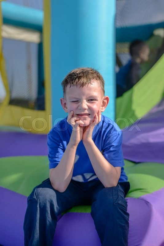 Stock image of 'Exhausted boy with sweaty face and hands near mouth in blue short sleeve shirt sitting near bouncy house entrance'