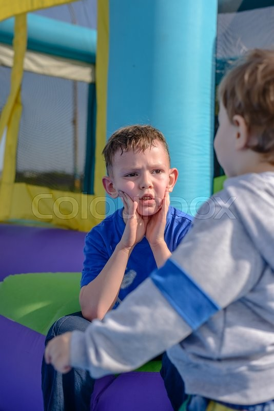 Stock image of 'Sweaty faced little boy in blue short sleeve shirt sitting with friend near bouncy house entrance'