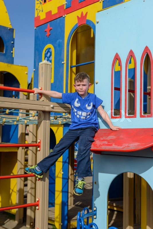 Stock image of 'Cute child in blue climbing down ladder pole on colorful little house at playground'