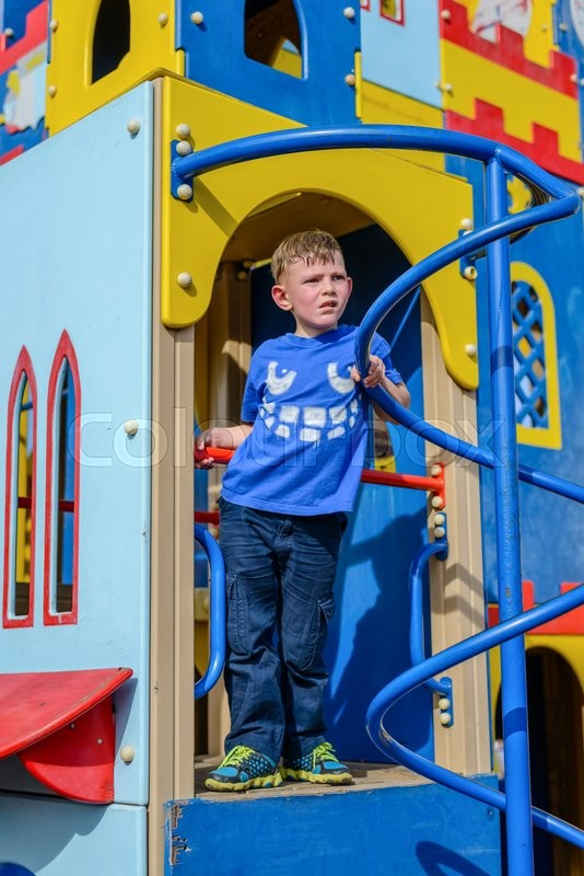 Stock image of 'Happy little boy in blue shirt and pants having fun on play castle with blue sky behind him'
