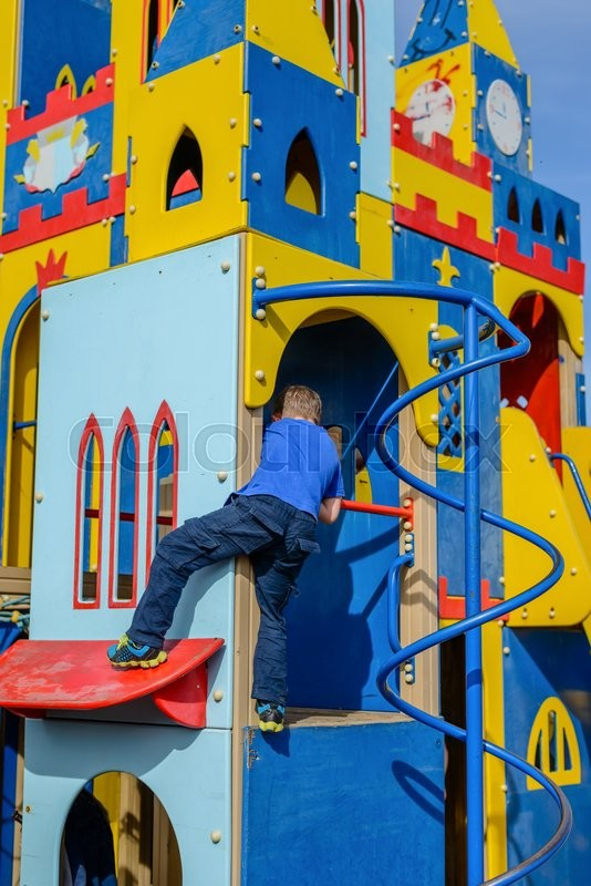 Stock image of 'Cute child in blue climbing up ladder pole on colorful castle house at playground'