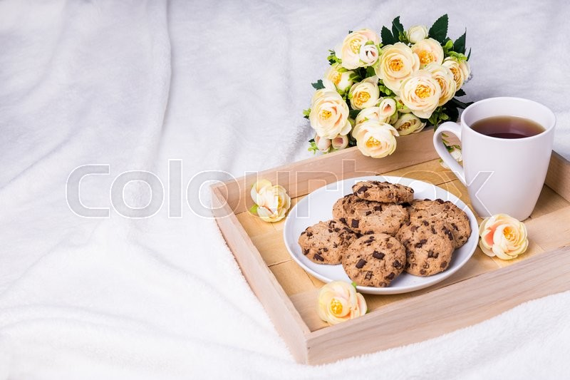 Stock image of 'close up of wooden tray with chocolate chip cookies, cup of tea and flowers over white background'