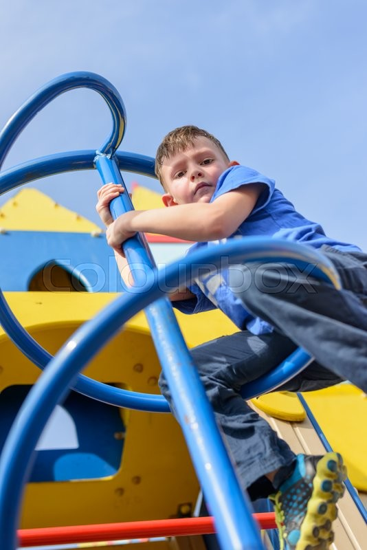Stock image of 'Low angle view on little boy in blue shirt and pants climbing twisted pole on play castle with blue sky behind him'
