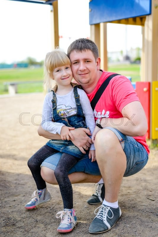 Stock image of 'Cute little blond girl in blue jean dress sitting on knee of father with playground behind them'