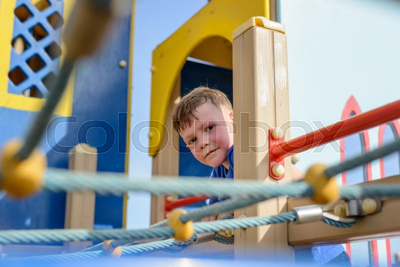 Stock image of 'Single cute sweating male child framed by climbing ropes peering from colorful playground house outdoors'