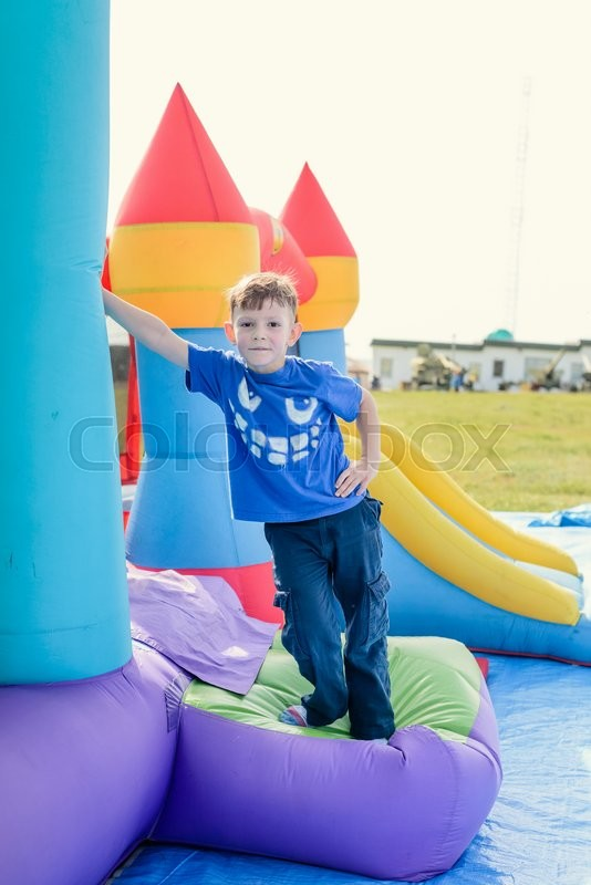 Stock image of 'Cheerful cute little boy with red hair, blue shirt and pants leaning against inflatable castle beside slide outdoors'