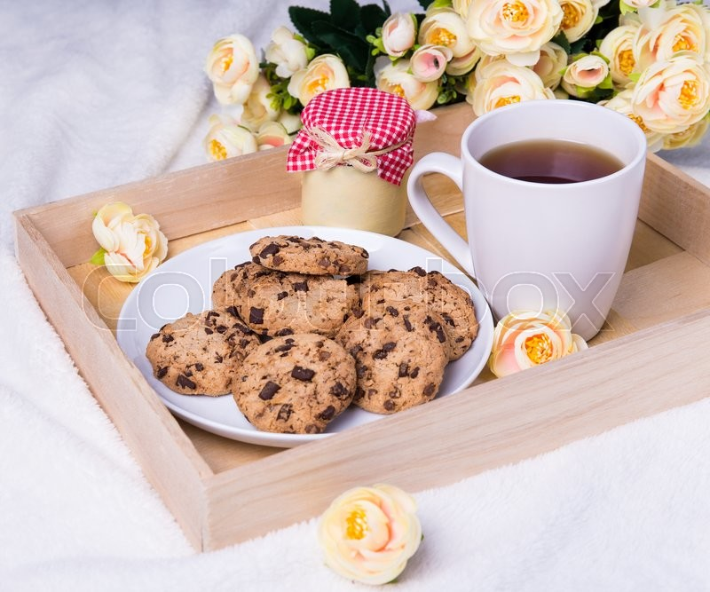 Stock image of 'close up of wooden tray with chocolate chip cookies, cup of tea, jam-jar and flowers over white background'