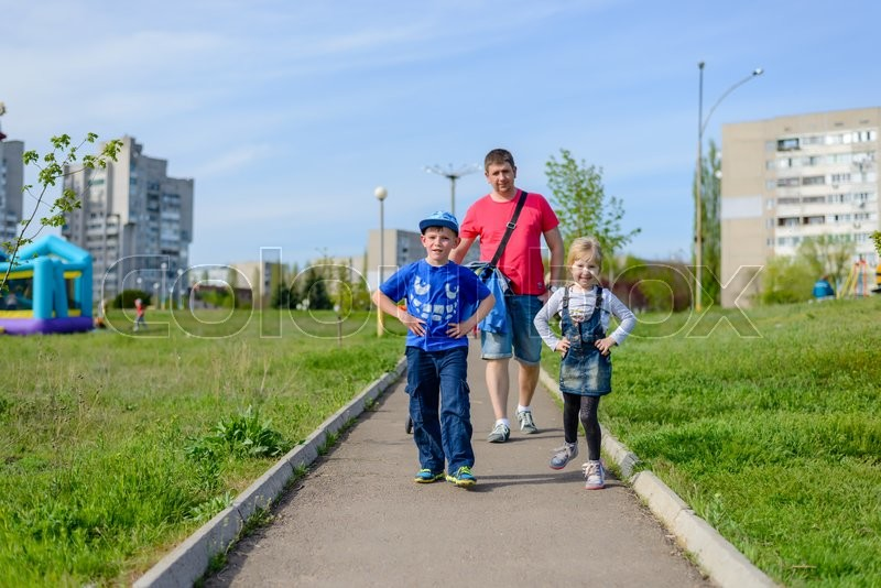 Stock image of 'Young father with two children, a happy grinning young boy and girl, going for a walk along a path through a green lush urban park'