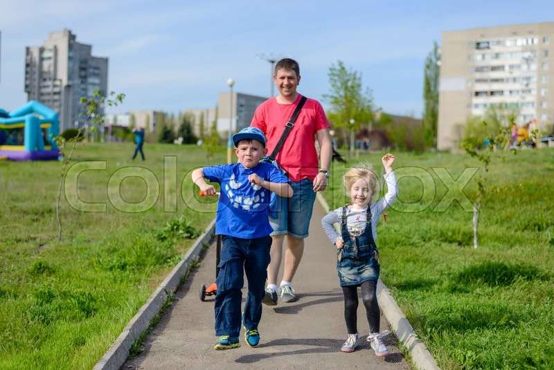 Stock image of 'Playful exuberant young children with their father laughing, running and jumping as they walk along a pathway through an urban park'