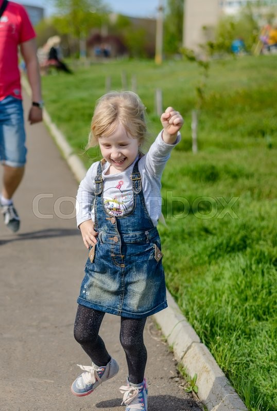 Stock image of 'Little boy and girl having fun outdoors laughing and jumping as they run along a path followed by their father in the background'