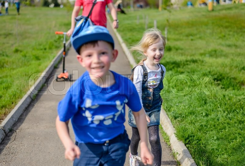 Stock image of 'Vivacious spontaneous pretty little blond girl running and laughing along a path with her brother as they go out to play in the sunshine, fathers legs visible behind'