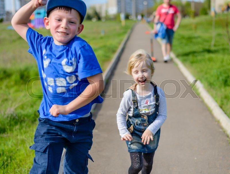 Stock image of 'Happy little boy and girl clowning around outdoors laughing and pulling faces as they run along a path through an urban path'