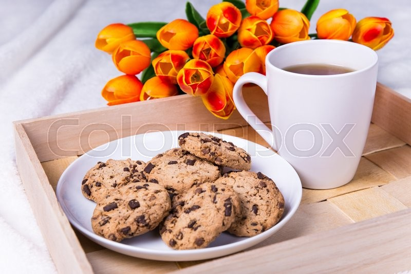 Stock image of 'close up of wooden tray with chocolate chip cookies and cup of tea'