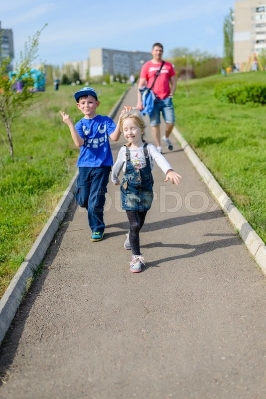 Stock image of 'Exuberant young boy and girl clowning outdoors as they run along a path in an urban park followed by their father'