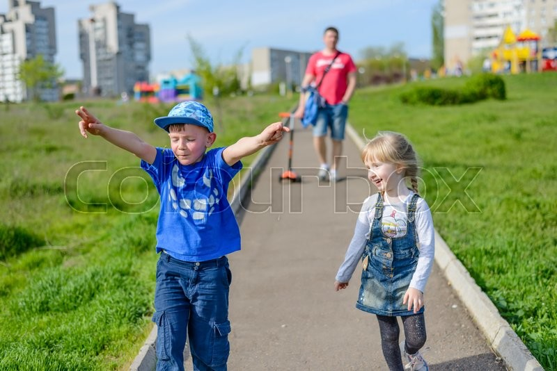 Stock image of 'Happy laughing young boy and girl running outdoors along a path through an urban park in spring sunshine followed by their father in the background'