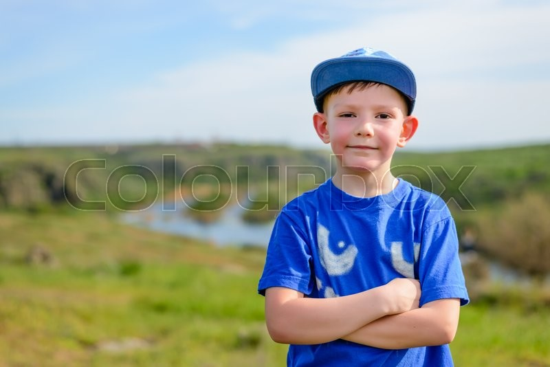 Stock image of 'Happy attractive confident young boy in a trendy blue outfit standing with folded arms grinning at the camera, countryside view with copy space'