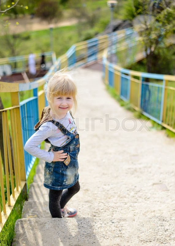 Stock image of 'Cute little blond girl climbing a steep flight of outdoor concrete stairs up a rural hillside pausing for a rest and smiling at the camera'