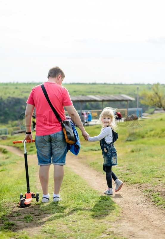 Stock image of 'Adorable little blond girl holding hands with her father as they walk along a rural path turning to look back and smile happily at the camera'