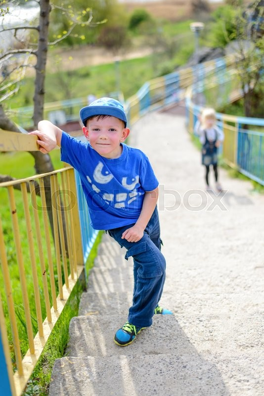 Stock image of 'Young boy in a trendy blue outfit pausing for a rest on steep flight of outdoor stairs on a rural hillside leaning on the rail and grinning up at the camera'