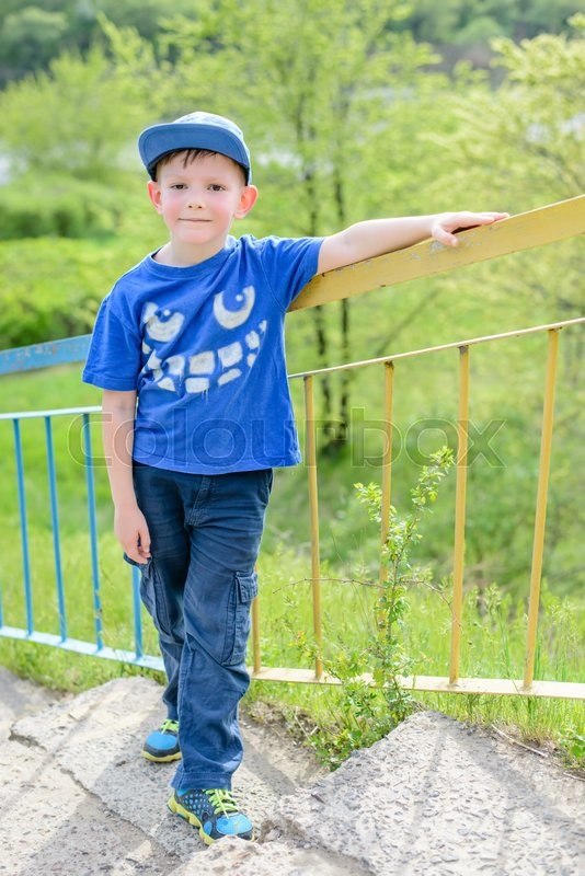 cute little blond boy in blue hat shirt and pants leaning on