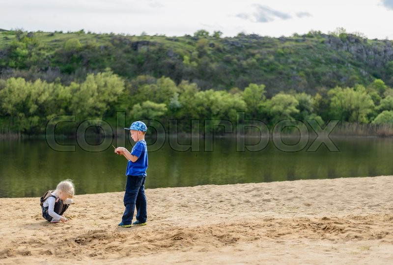 Stock image of 'Little boy in hat and blond girl playing on sand near river edge with short tree lined hill in background with copy space'