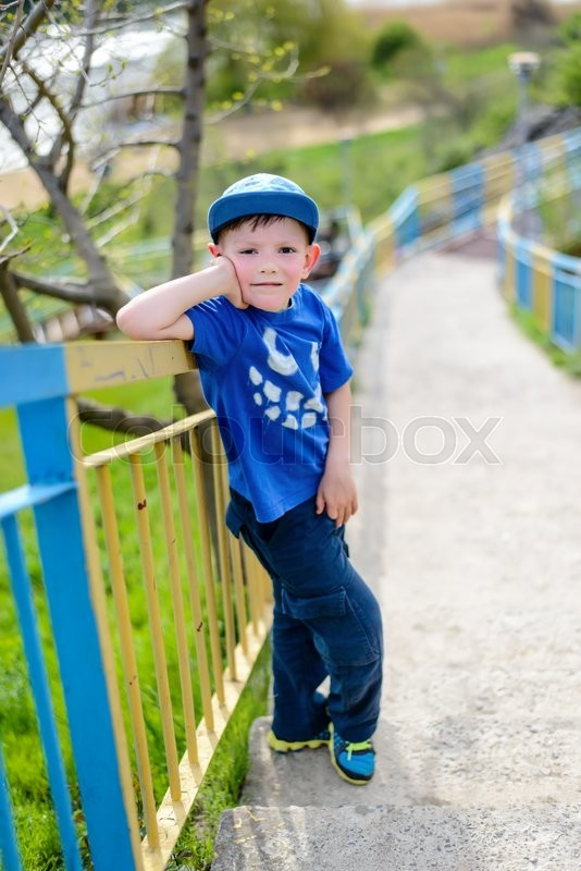 Stock image of 'Cute little blond boy in blue hat, shirt and pants leaning on railing at hill outside during summer'