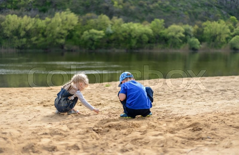 Stock image of 'Little boy in hat and blond girl digging into sand near river edge with short tree lined hill in background with copy space'