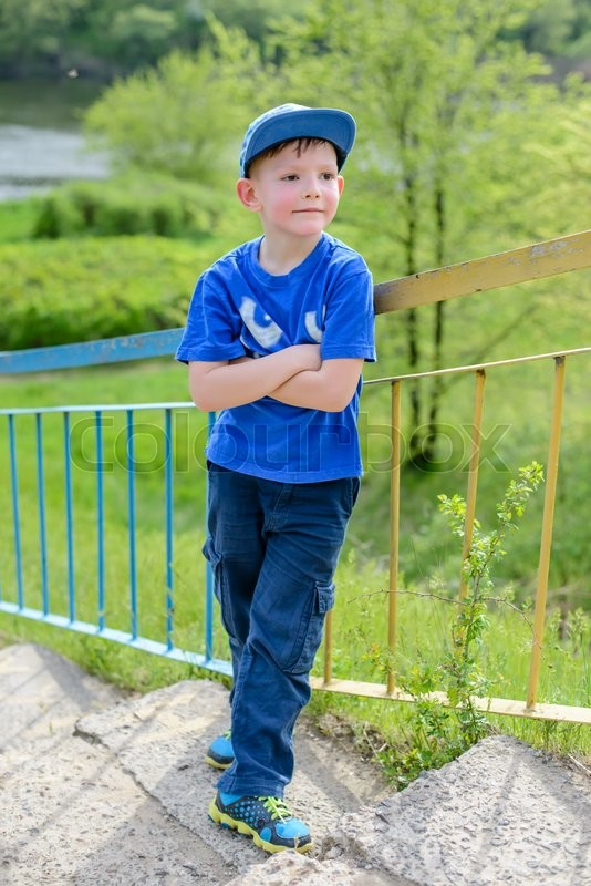 Stock image of 'Cute little blond boy in blue hat, shirt and pants leaning on railing with folded arms at hill outside during summer'