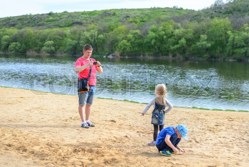 Stock image of 'Parent takes photos of children on the beach by quiet lake and nearby hills on a beautiful summer day'