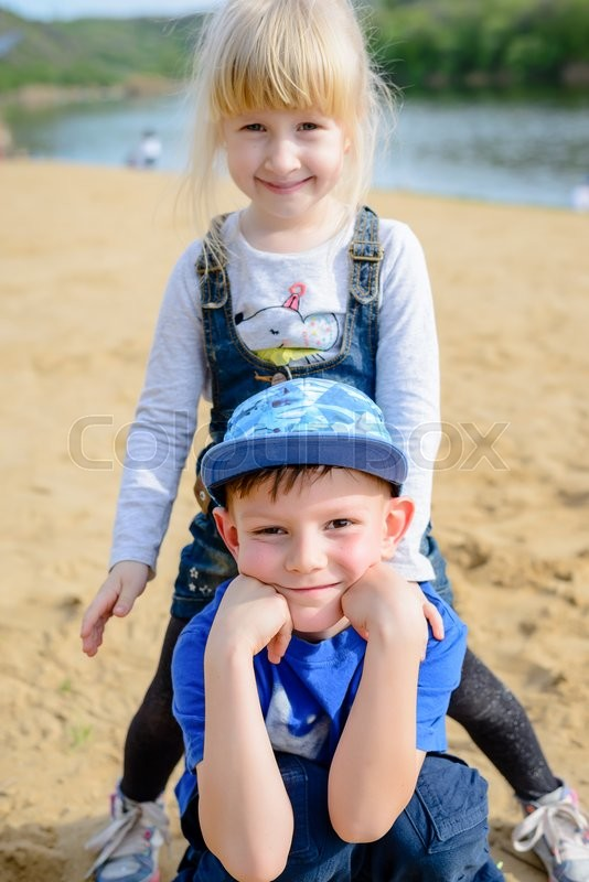 Stock image of 'Smiling young boy and pretty little blond girl relaxing on a sandy beach alongside a lake or river posing for the camera'
