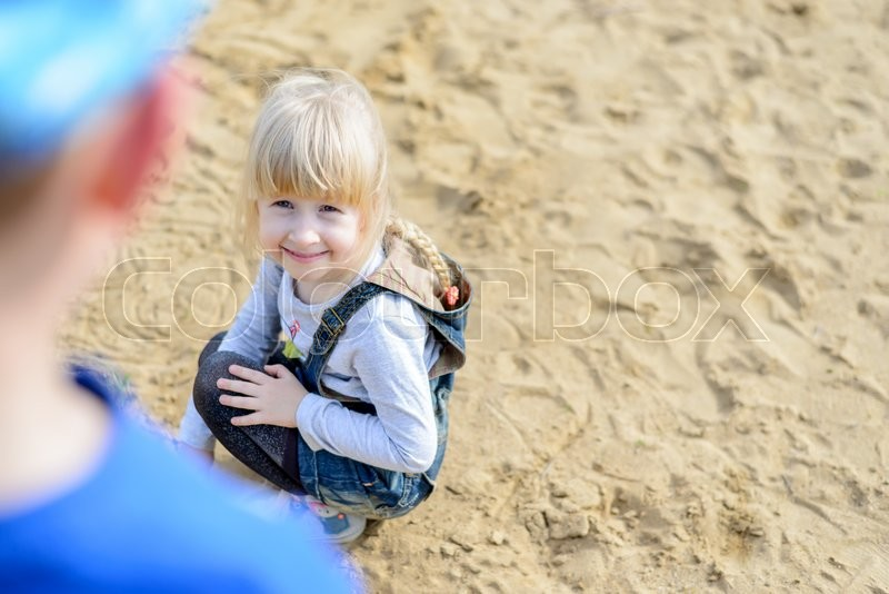 Stock image of 'Overhead view of child kneeling in the sand on the beach while her parent looks down on her'