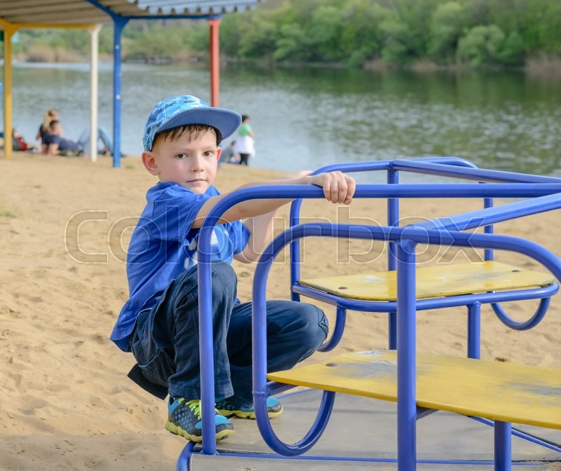Stock image of 'Young boy crouching on a colorful blue merry-go-round looking jauntily at the camera on a sandy beach near a lake or river'