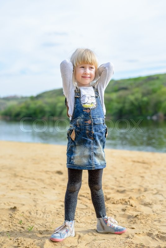 Stock image of 'Cute pretty little blond girl with a lovely smile holding her hands raised behind her head as she poses for the camera outdoors with copy space'