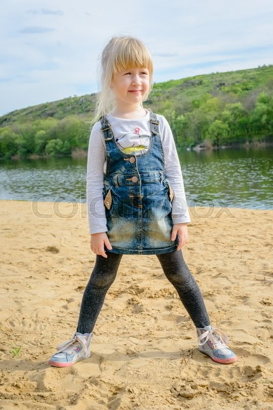 Stock image of 'Cute little blond girl standing on a sandy beach in a denim skirt and leggings smiling happily as she looks to the side'