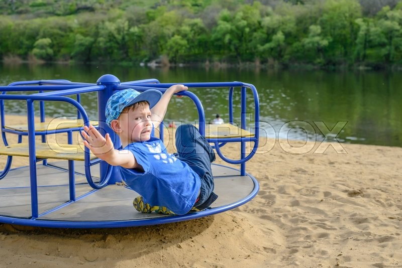 Stock image of 'Little boy on a spinning merry-go-round waving at the camera as he looks back over his shoulder outdoors on a sandy beach near a watercourse'