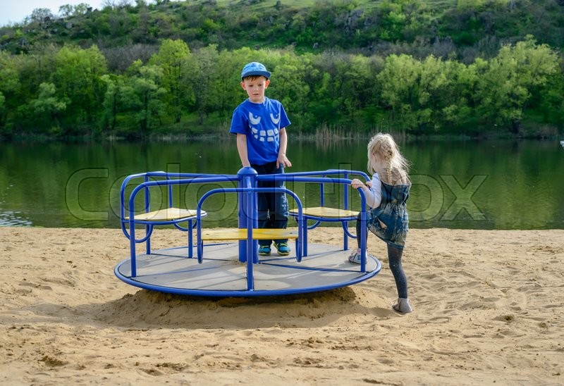 Stock image of 'Two young kids playing on a blue merry-go-round on a sandy beach alongside a lake as they enjoy their summer vacation'