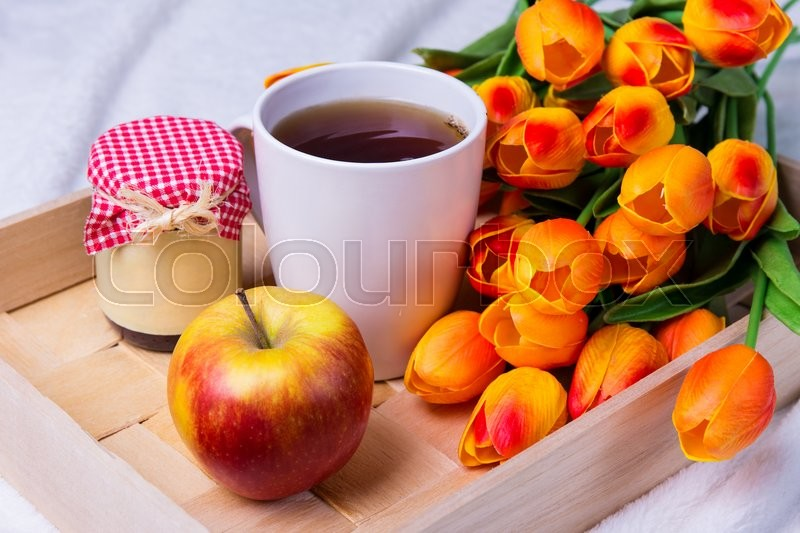 Stock image of 'close up of wooden tray with cup of tea, jam-jar, apple and flowers'